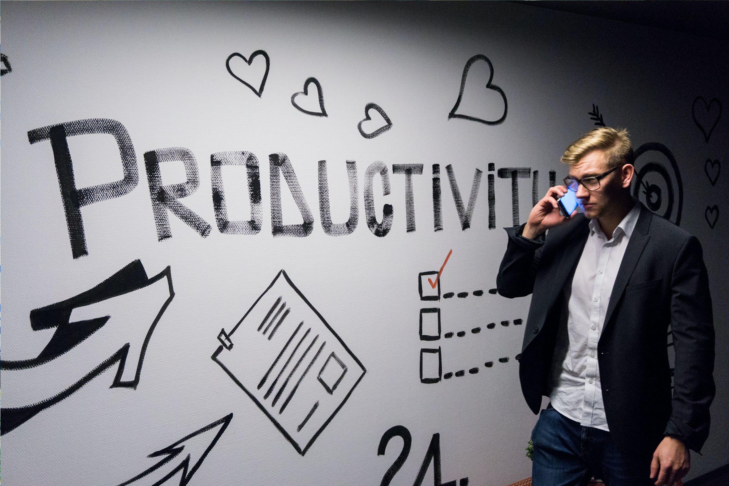 站在寫著productivity牆前面打電話的白人